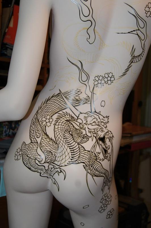 Peinture aérographe en cours sur mannequin vue dos motif dragon